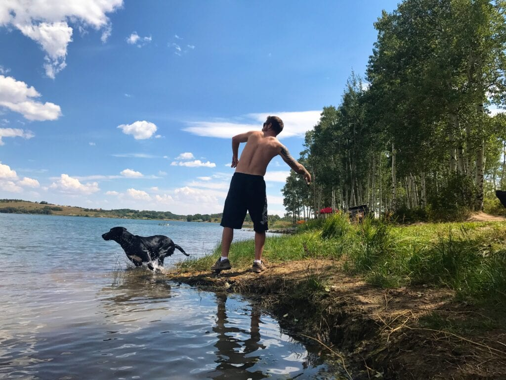 Man playing fetch with dog in water at Kolob Reservoir