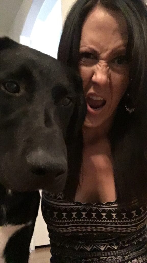 girl with funny face taking a picture with her dog
