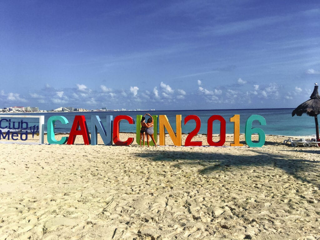 Girls posing together in front of the Cancun 2016 sign on the beach in Mexico