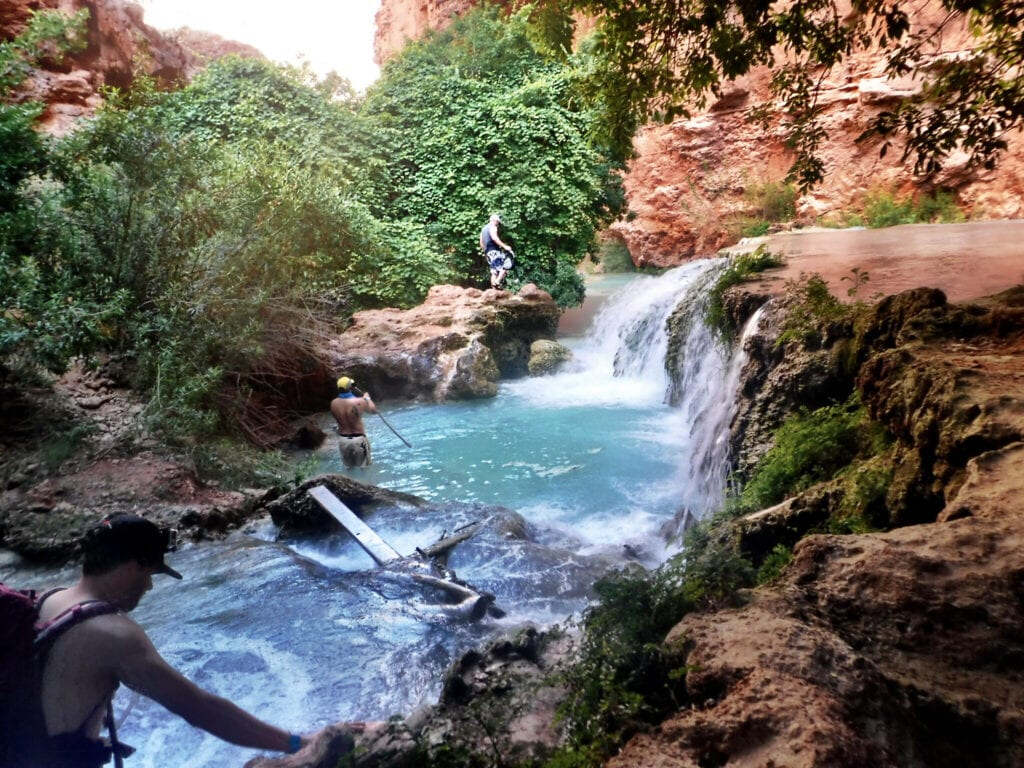 waterfall with lush greenery man walking The Grand Canyon, Arizona