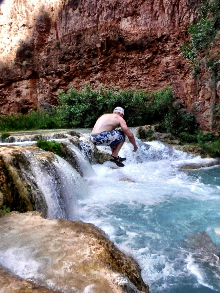 man jumping into the water havasupai The Grand Canyon, Arizona
