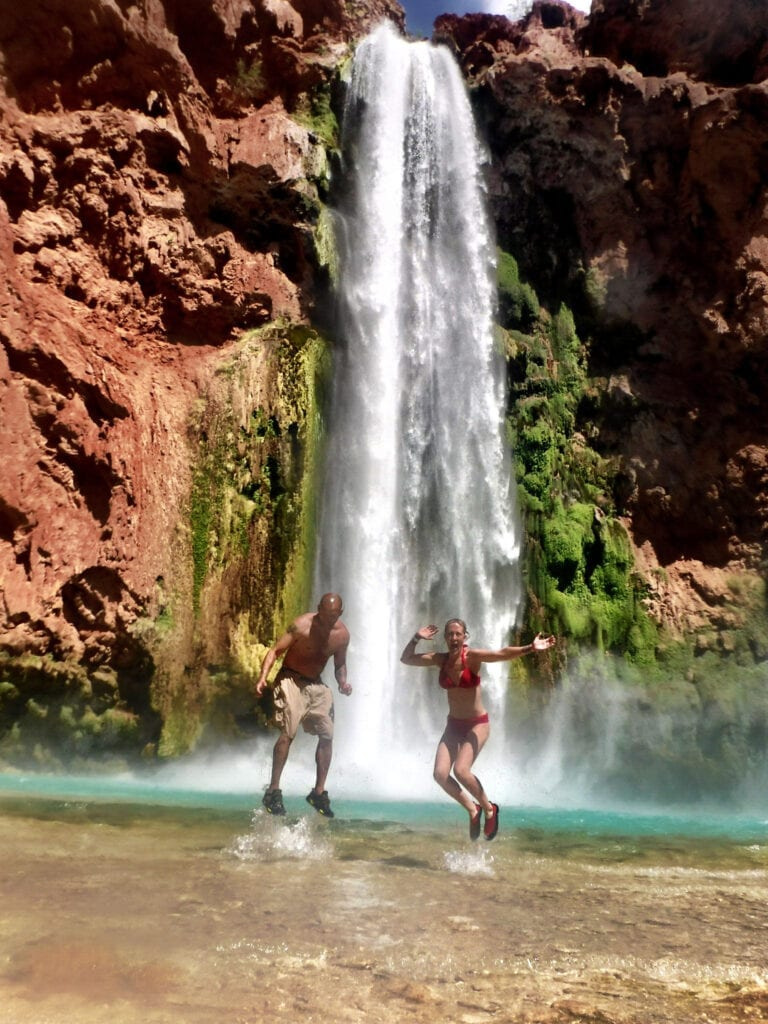 man and woman jumping in front of Havasu Falls waterfall The Grand Canyon, Arizona
