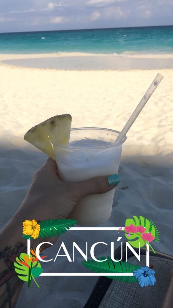 Hand holding pina colada with pineapple slice at the beach