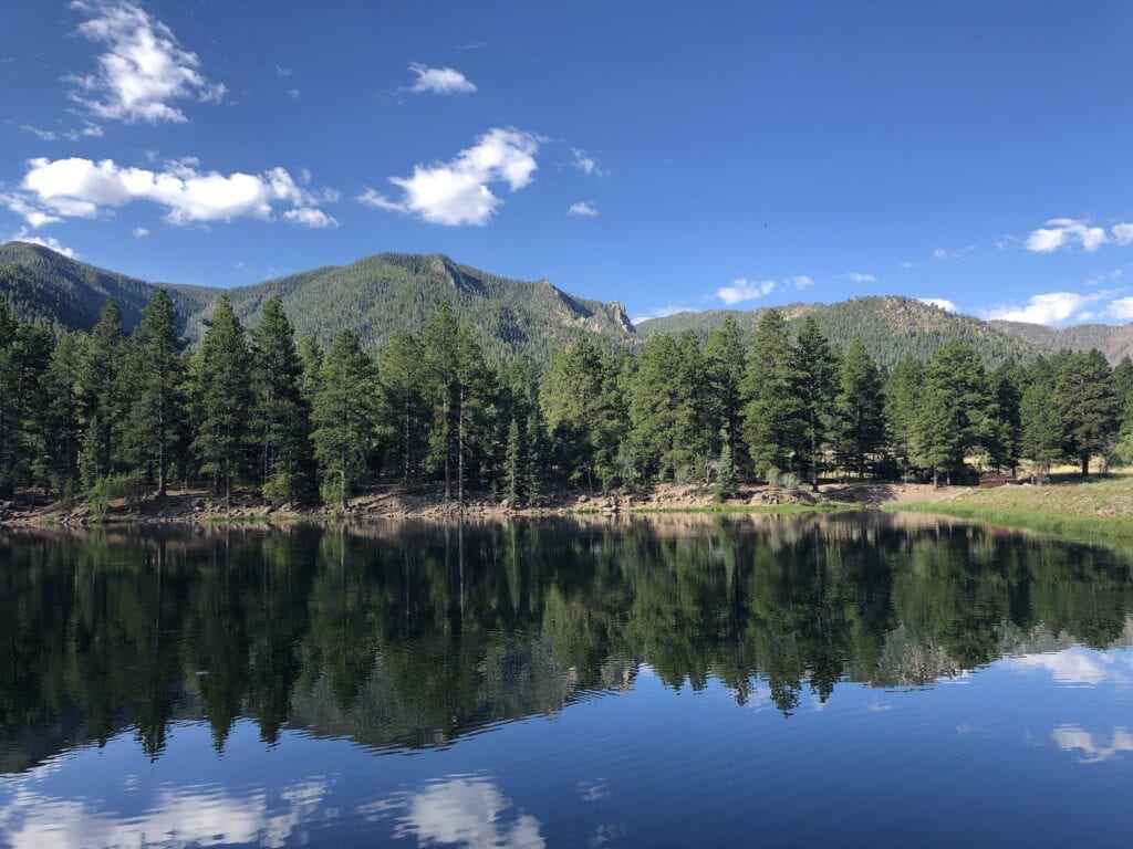 Pine Valley Reservoir, Utah. Mountain landscape with pine trees. Reflection of the trees and mountains against the water and sky