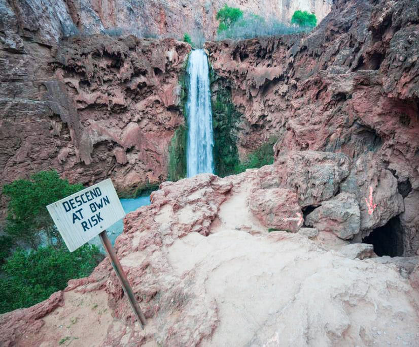 Mooney Falls, Descend at your own risk sign before hiking down, waterfall against the red cliffs in The Grand Canyon, Arizona
