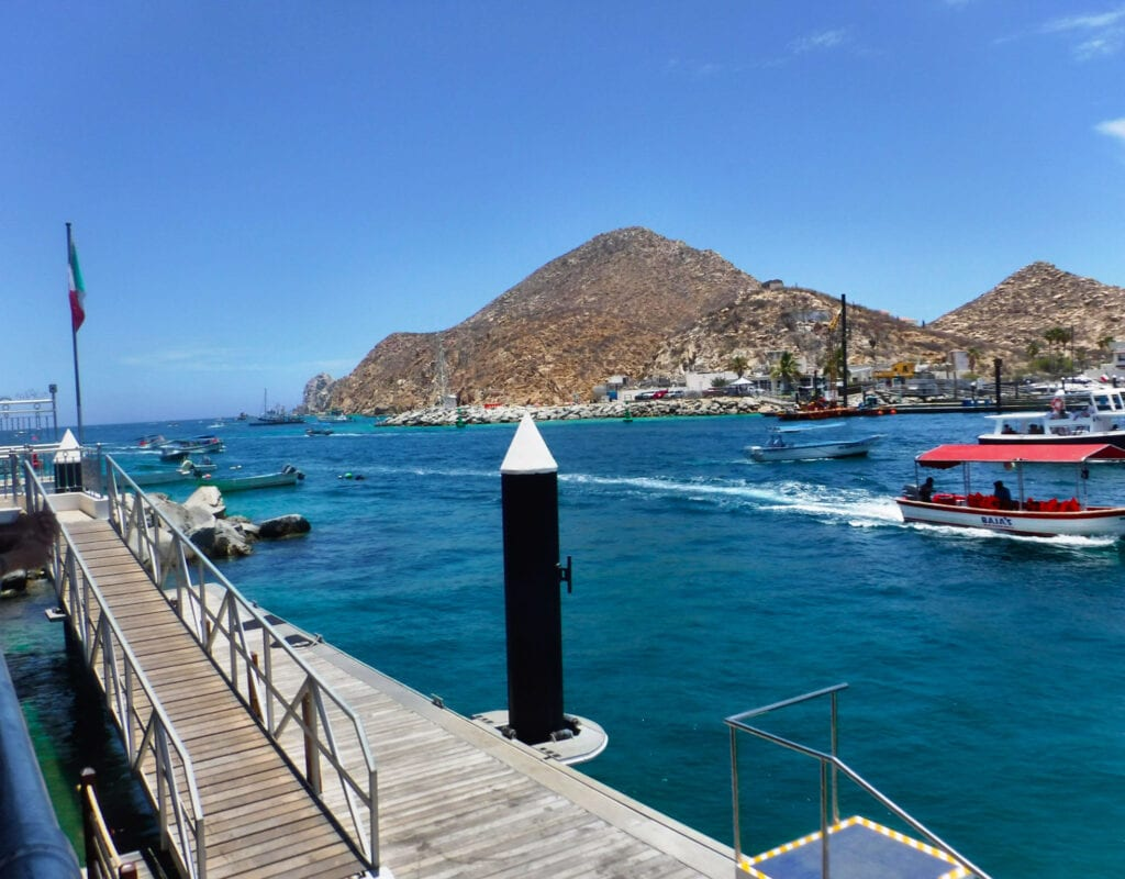 pier against the ocean with mountains in Cabo San Lucas, Mexico, ocean and boats