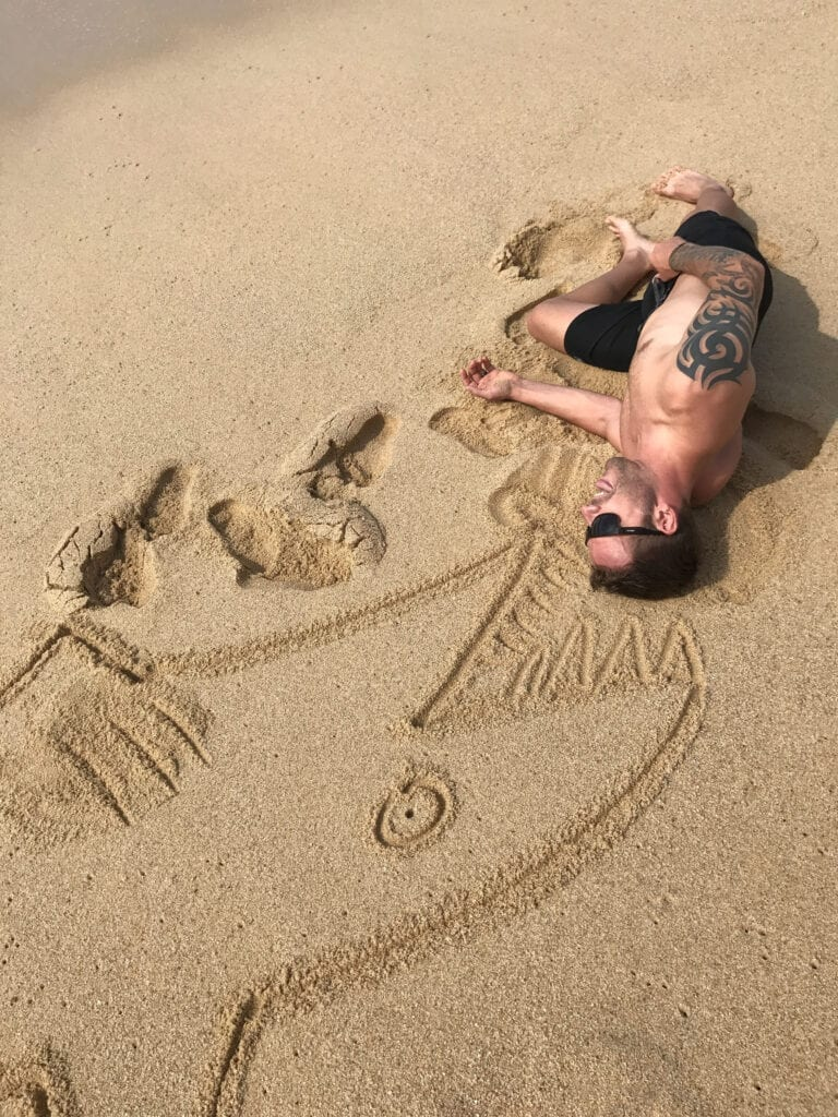 creative beach shot, shark drawn in the sand eating man in he Rui Hotel and Resort, Cabo San Lucas, Mexico