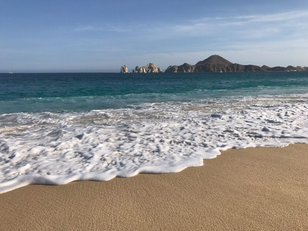 Beach and ocean against the sky with mountains at the Rui Hotel and Resort, Cabo San Lucas, Mexico