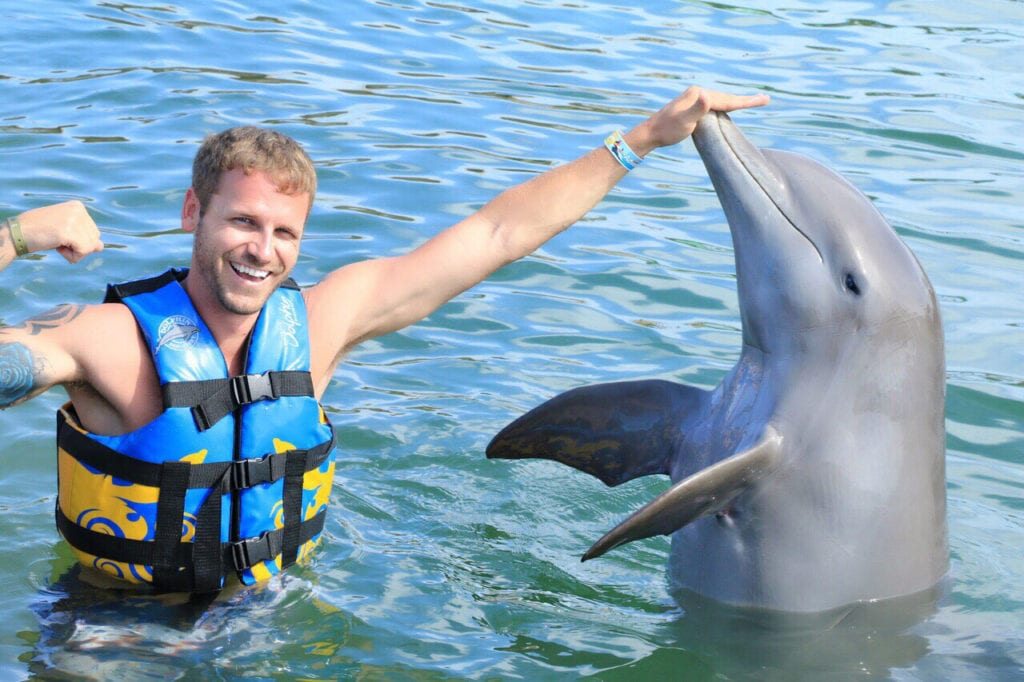 man posing with dolphin and touching its nose Cabo San Lucas, Mexico