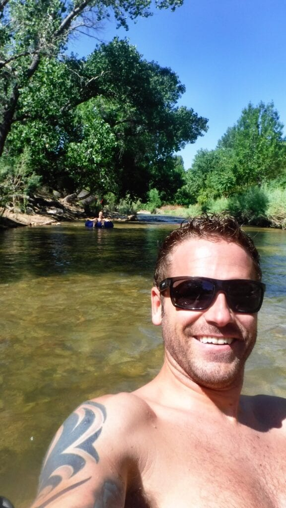 Man smiling and floating on the Virgin River near Zion National Park, Utah
