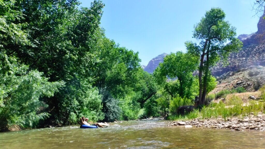 Man on a tube floating down the Virgin River near Zion National Park, Utah