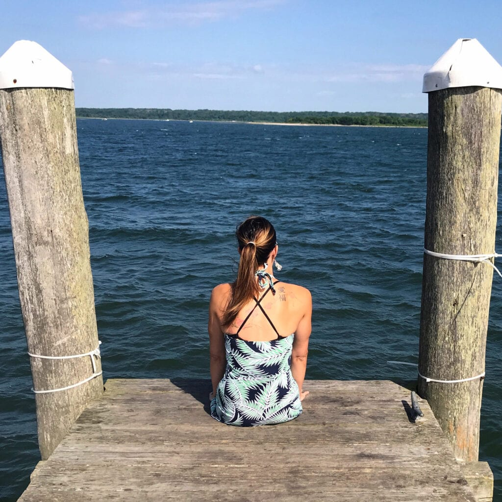 Girl sitting on dock looking out over the ocean