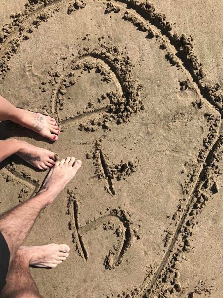 """J+D"" written in the sand with feet on the beach"