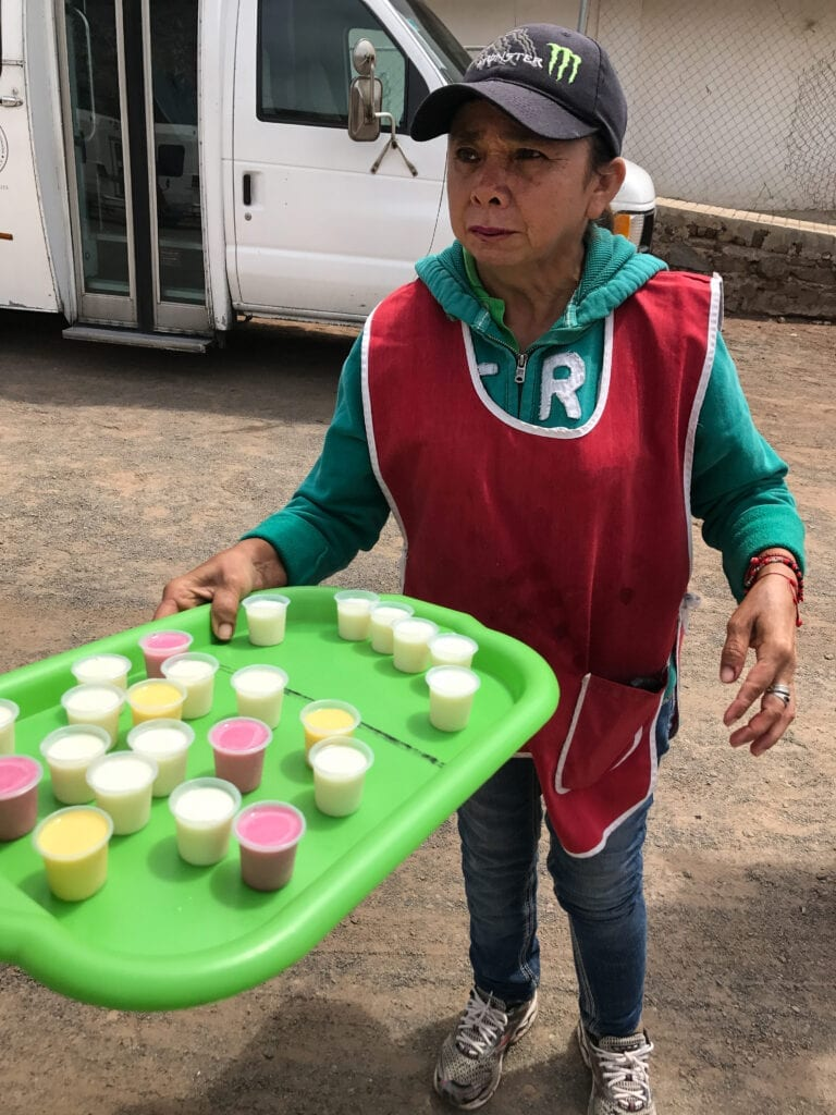 Hispanic woman handing out drink samples in Mexico