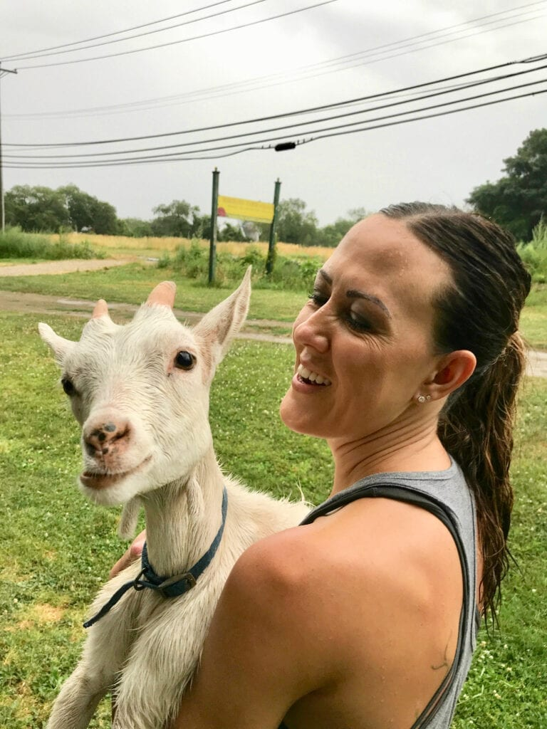 Girl holding goat with funny face