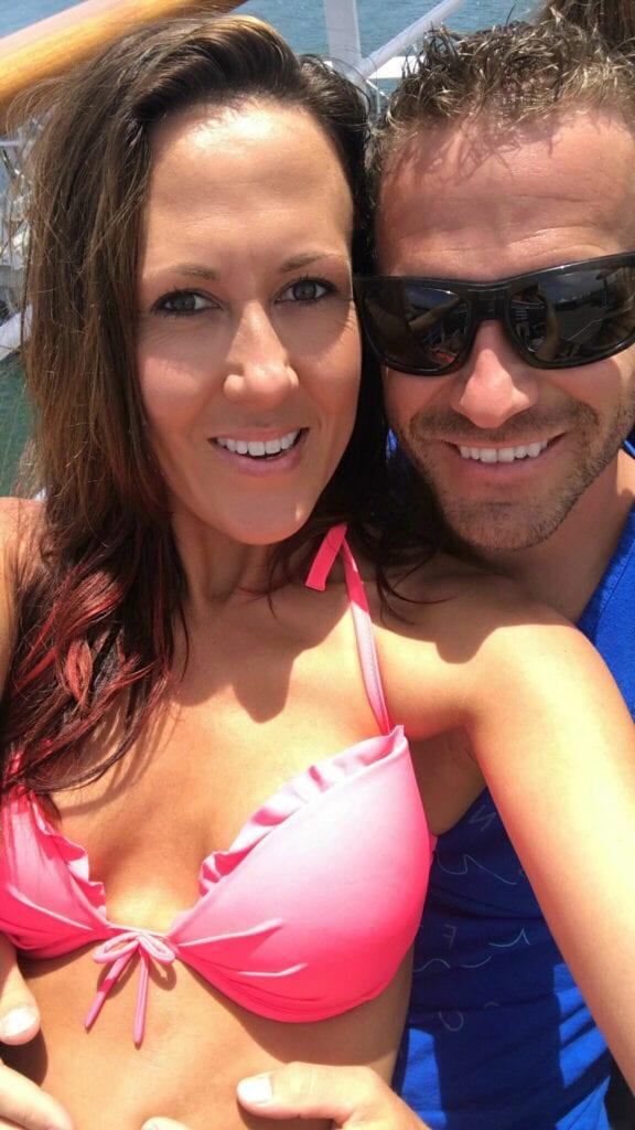 Girl in bikini smiling with man on cruise ship