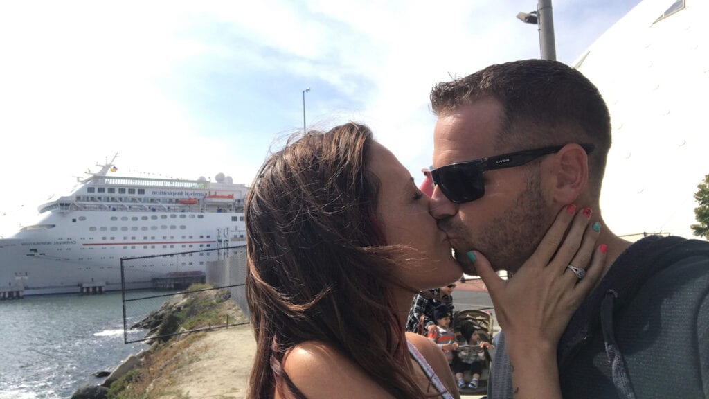 Man and woman kissing in front of cruise ship in Long Beach, CA