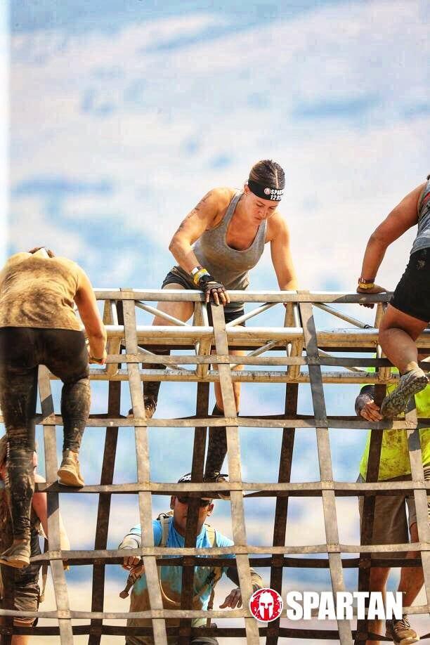 Women climbing over high rails during a Spartan Race