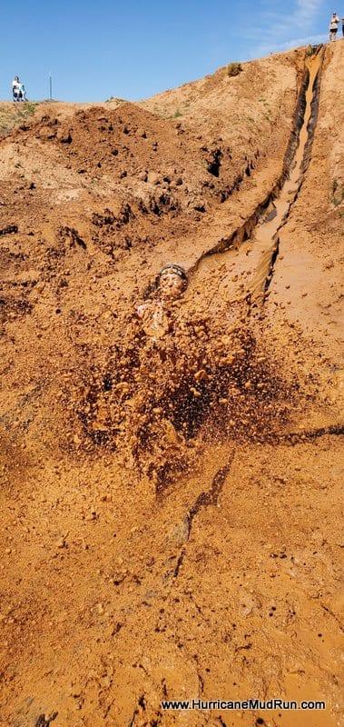 Girl sliding down mud slide and ending in muddy water
