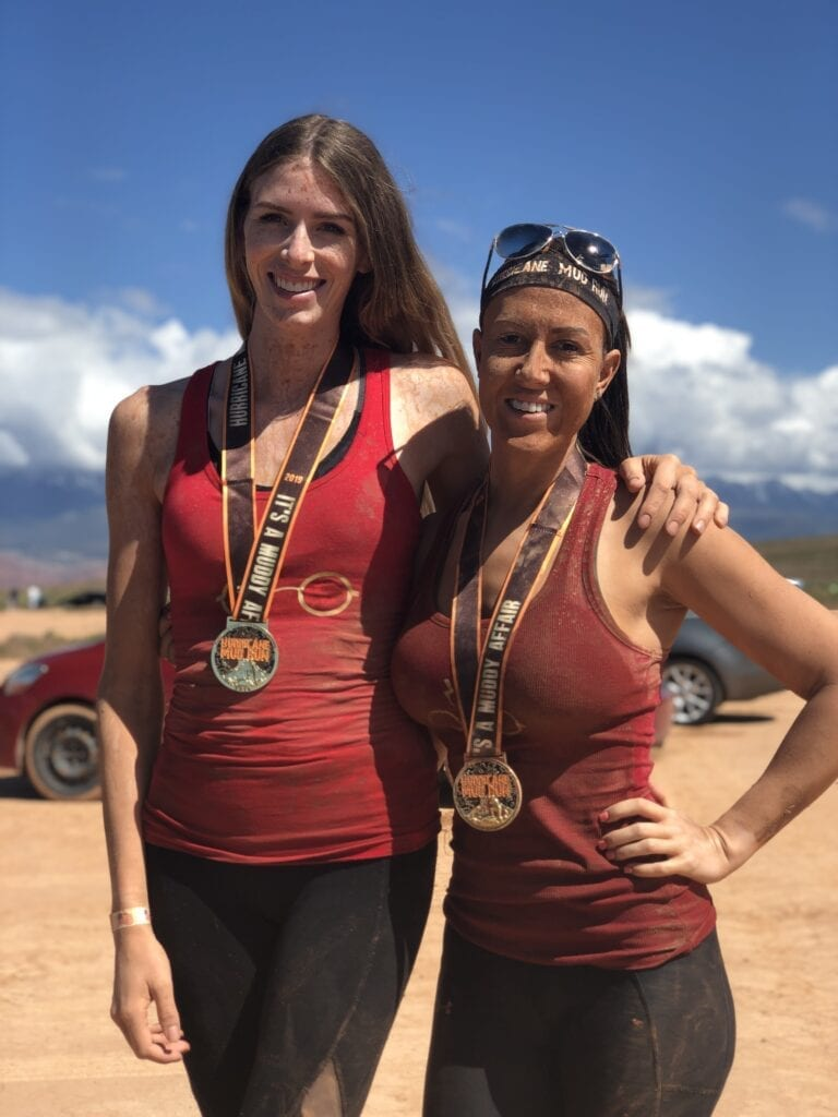 Girls posing with medals after completing Mud Run