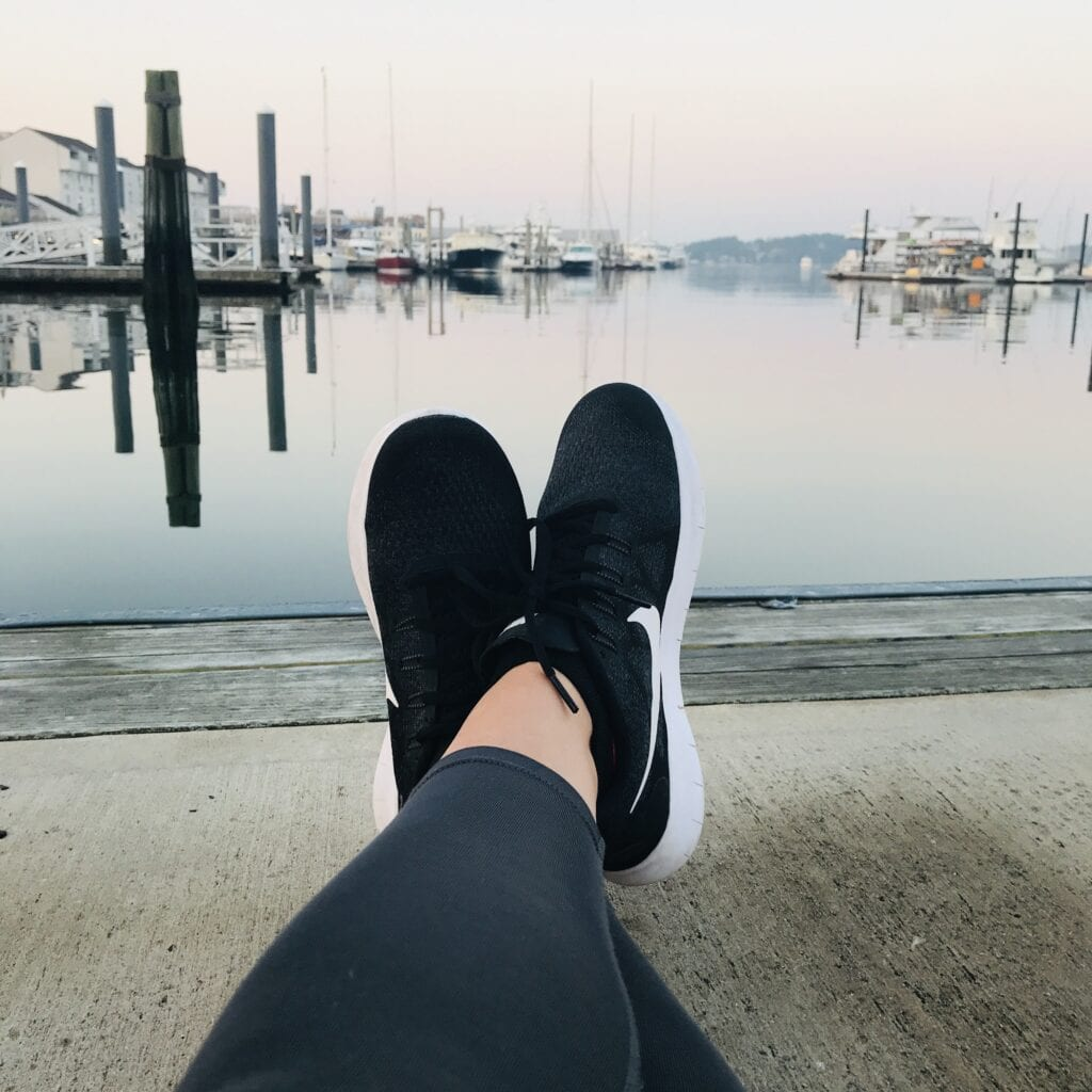 Girl's legs kicked out relaxing on the pier overlooking Newport Harbor
