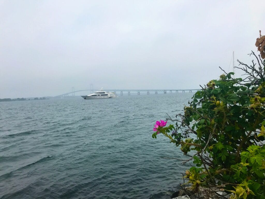 View of the ocean with a boat in the water and a bridge with a flower in front, Goat Island Marina, Newport, Rhode Island
