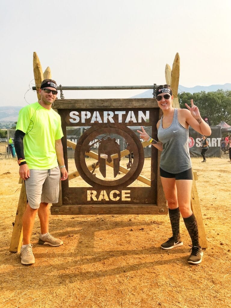 "Man and woman standing in front of ""spartan race"" sign"