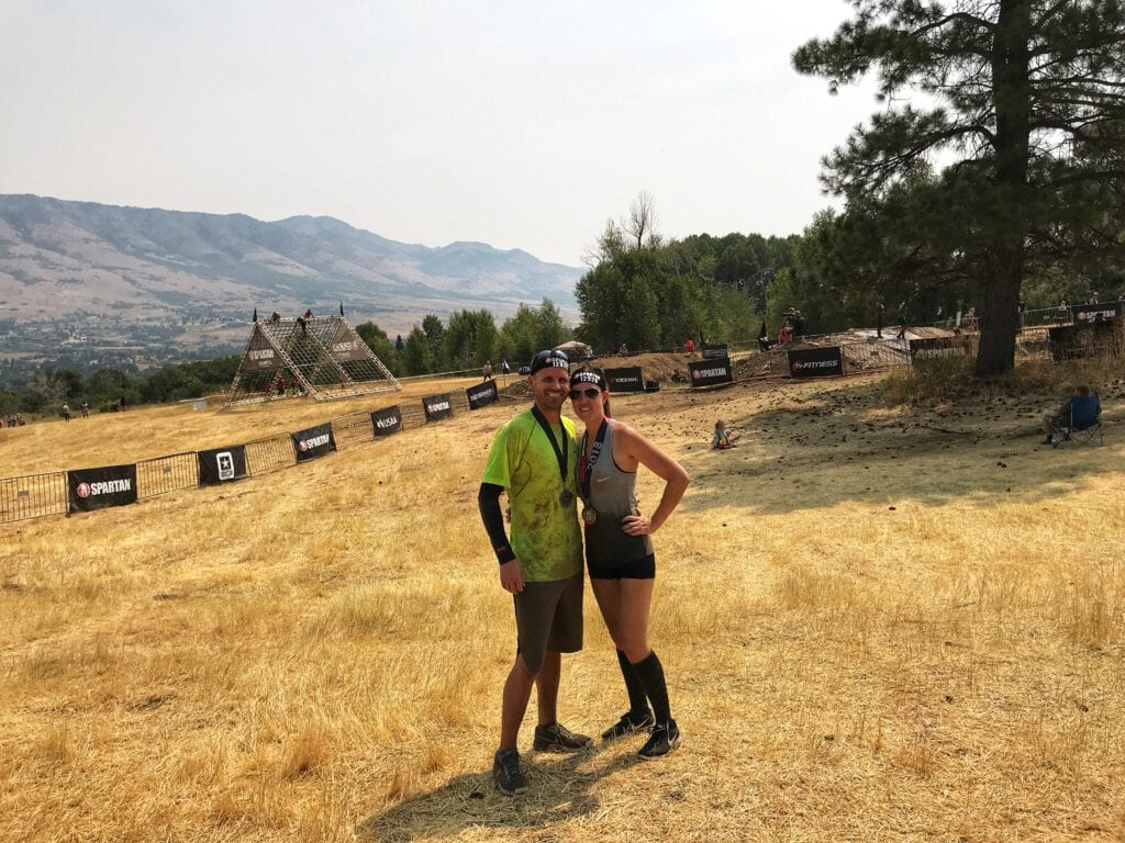 man and woman posing after completing Spartan Race