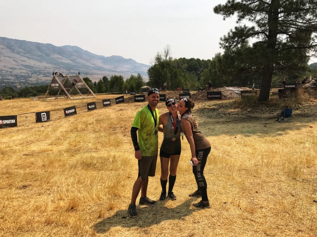 People posing, girl kissing girl's cheek after Spartan Race