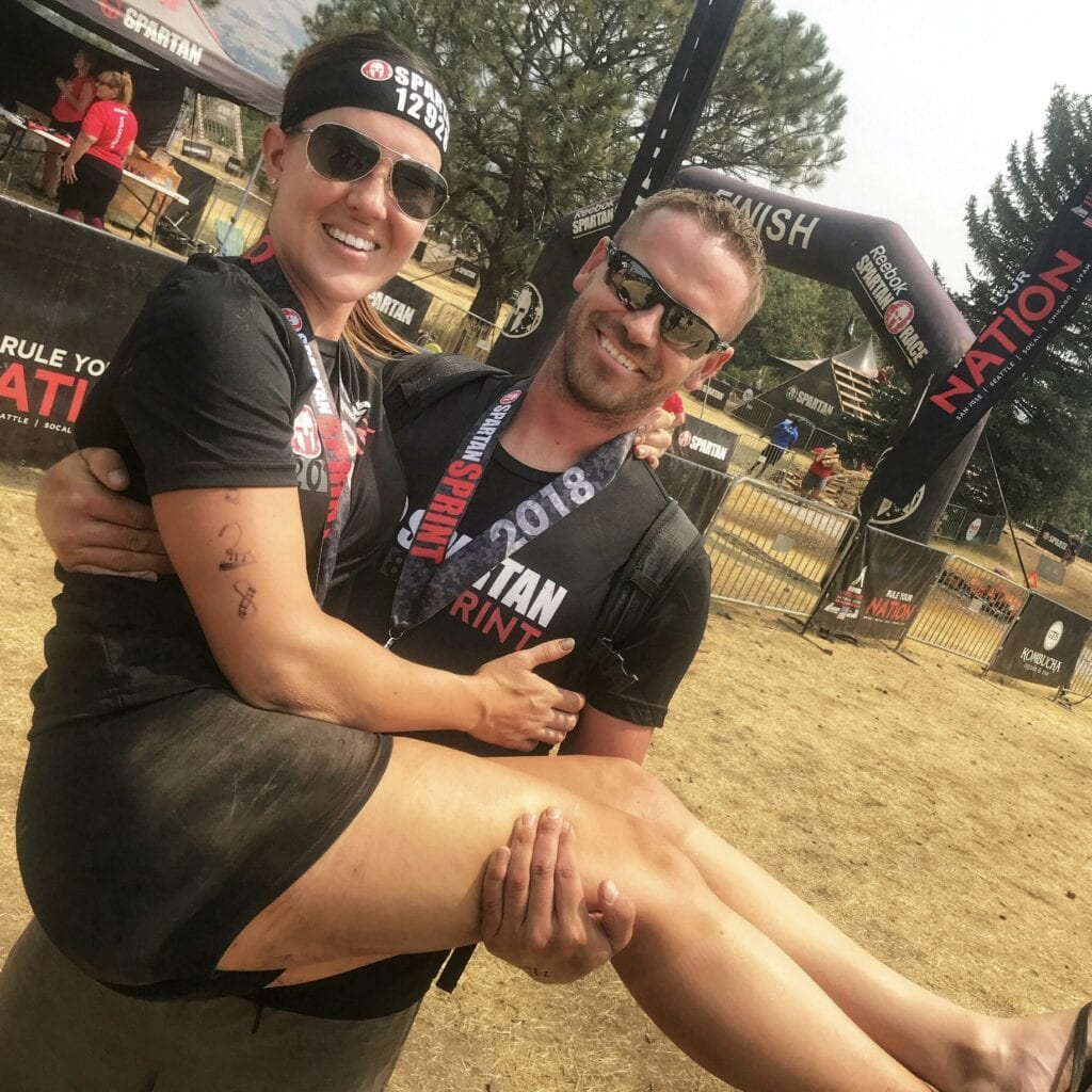 Man and woman posing with medals after Spartan Race