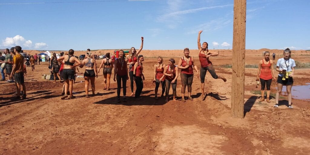 Girls posing and jumping at the end of mud run experience