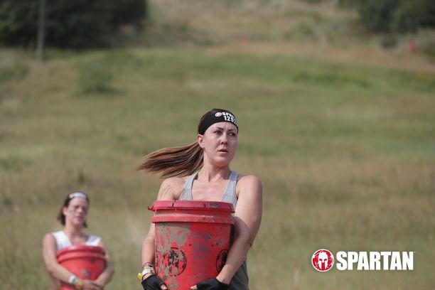 Woman carrying heavy bucket during Spartan Race