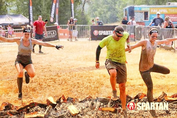 People jumping over fire at the end of Spartan Race