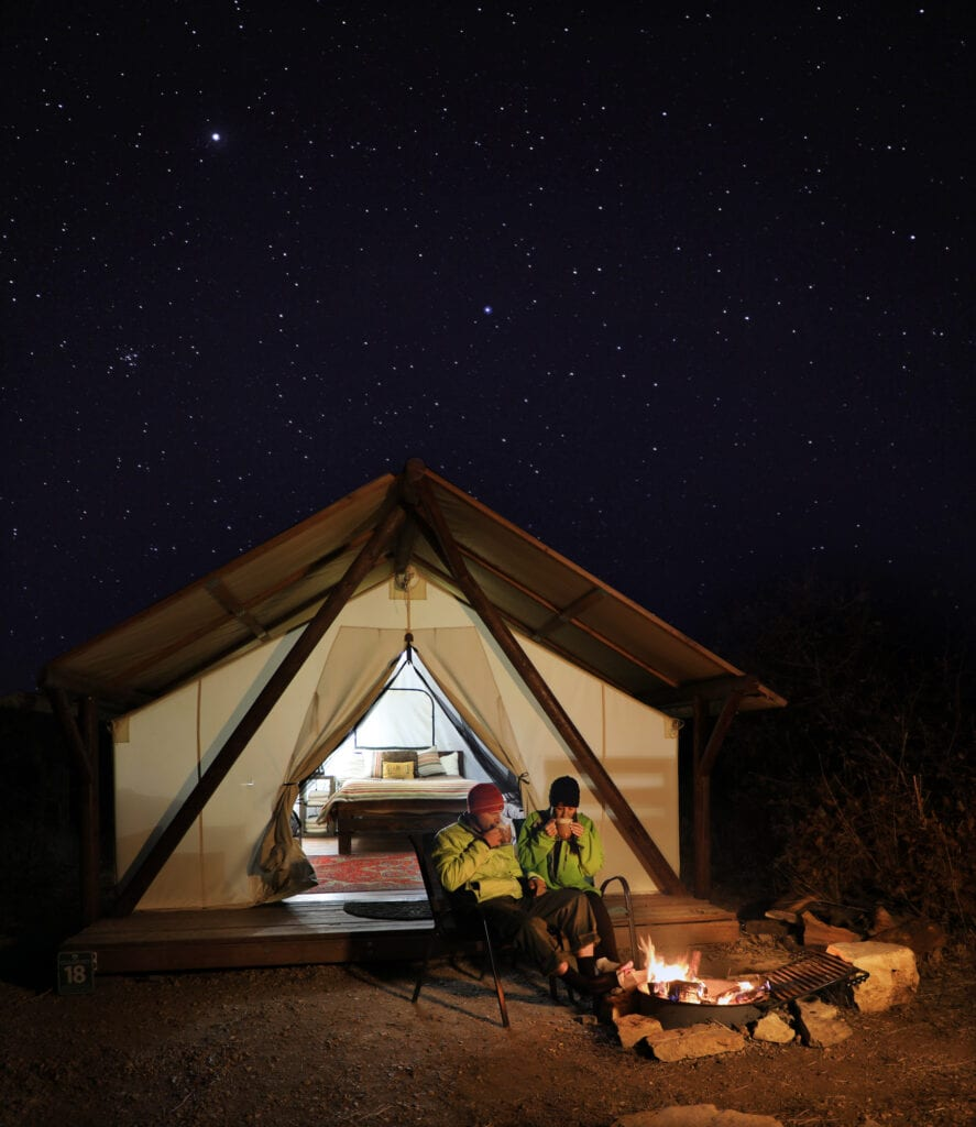 Couple glamping under the stars with campfire