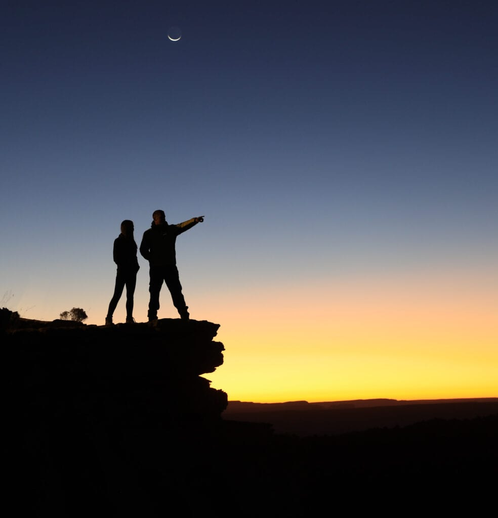 two people standing in a sunrise silhouette
