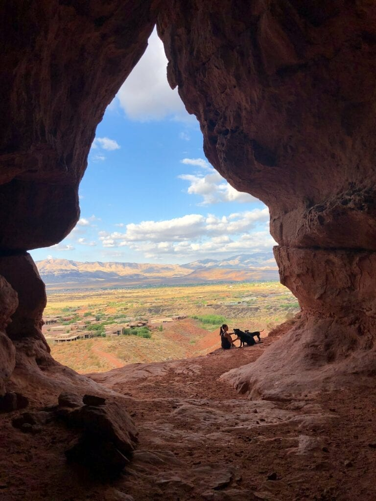 Views from inside a cave overlooking the city with a girl and her dog