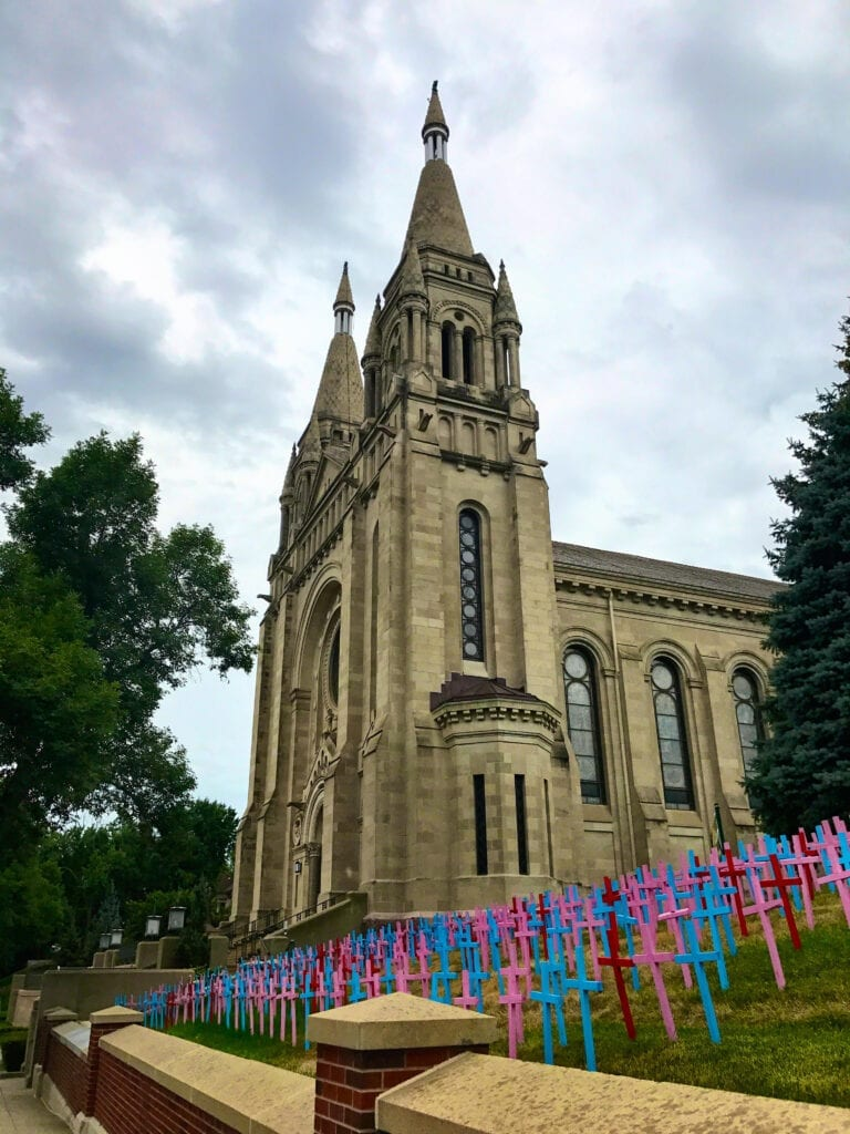 St Joseph Cathedral against the sky with wooden crosses on the ground, Sioux Falls, SD
