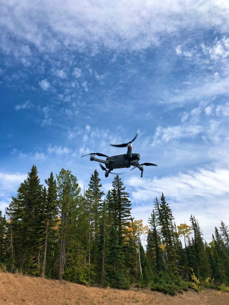 Drone flying in the sky in the mountains above pine trees with fall colors