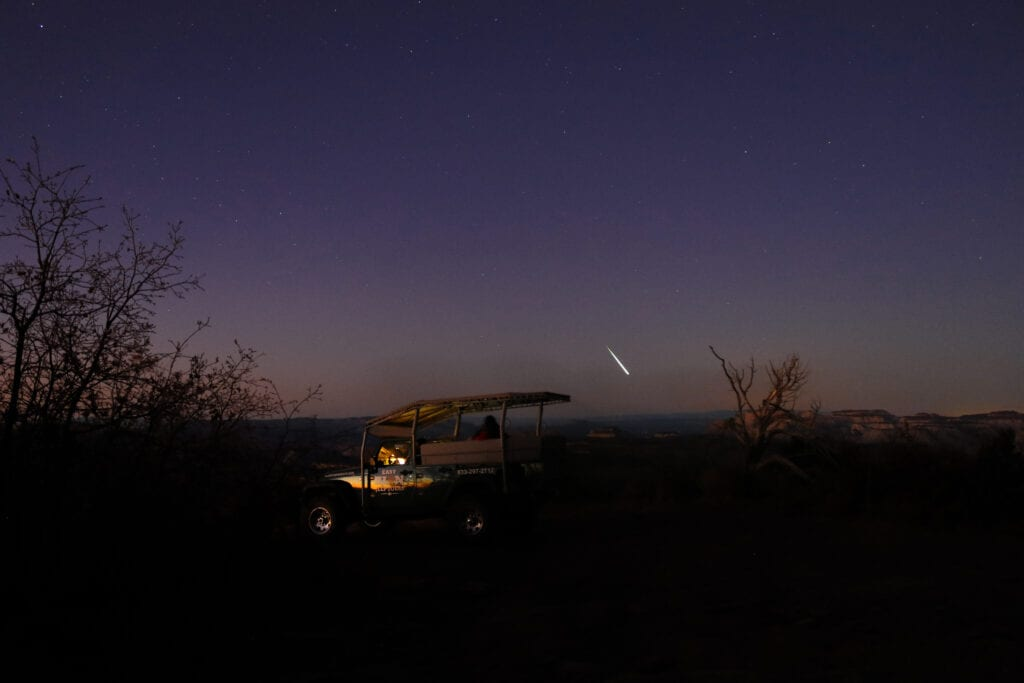shooting star over jeep mountain landscape