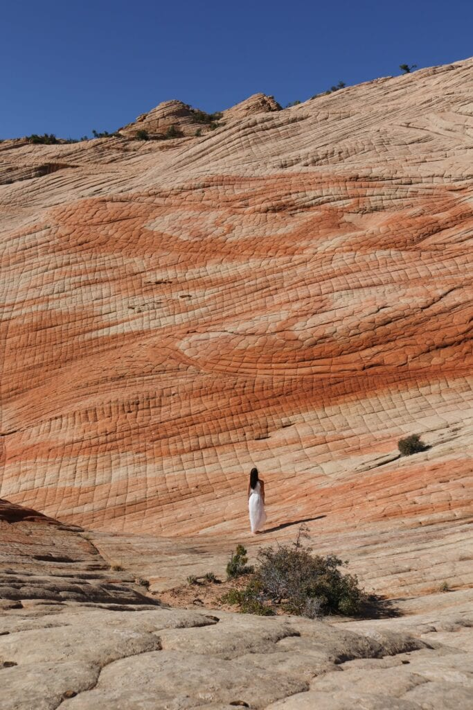 girl standing under sandstone formations