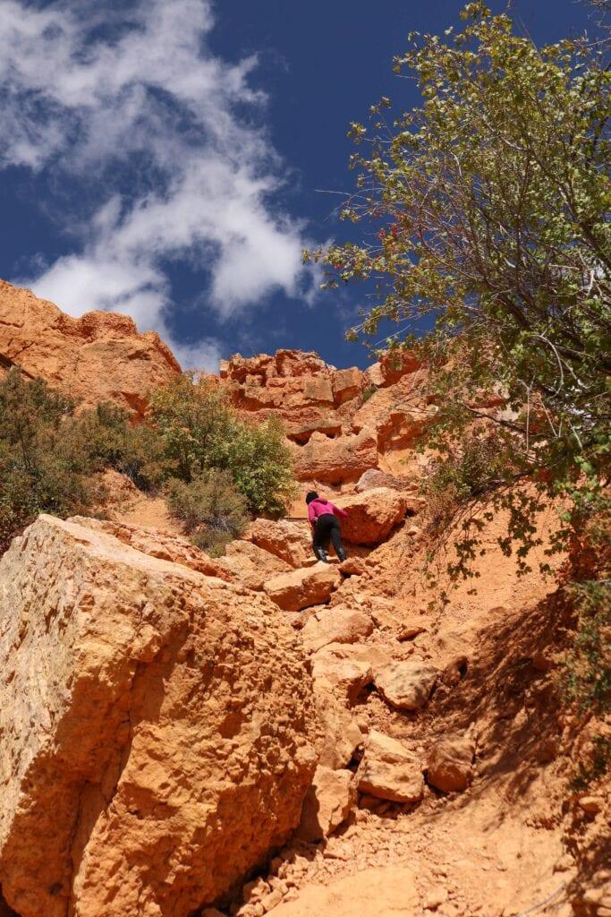 girl climbing red rocks hiking
