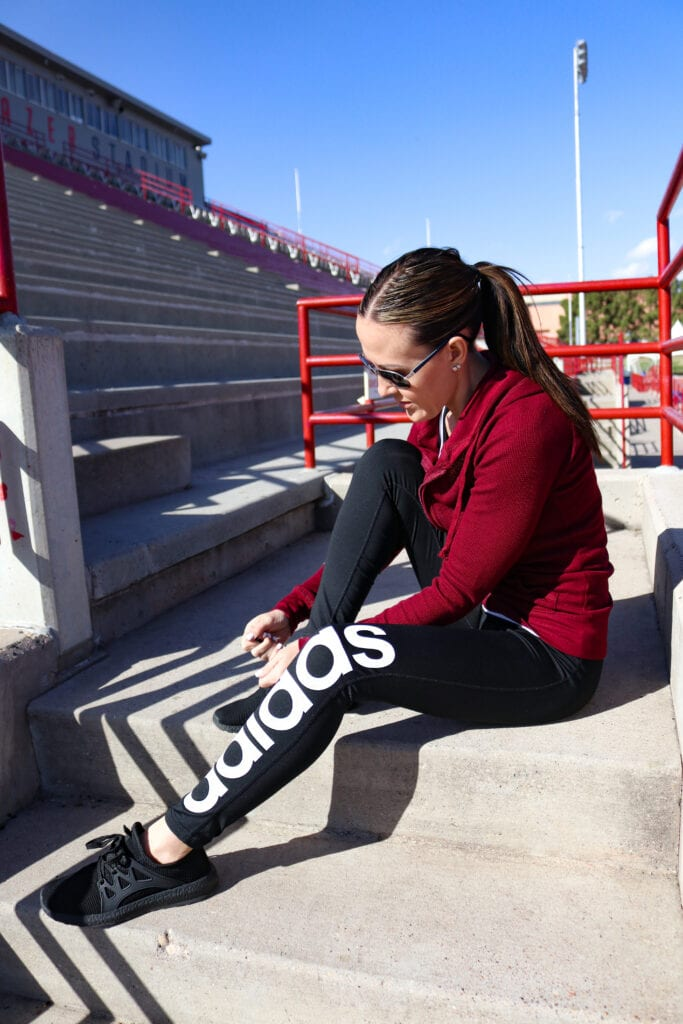 girl tying shoes wearing adidas workout leggings