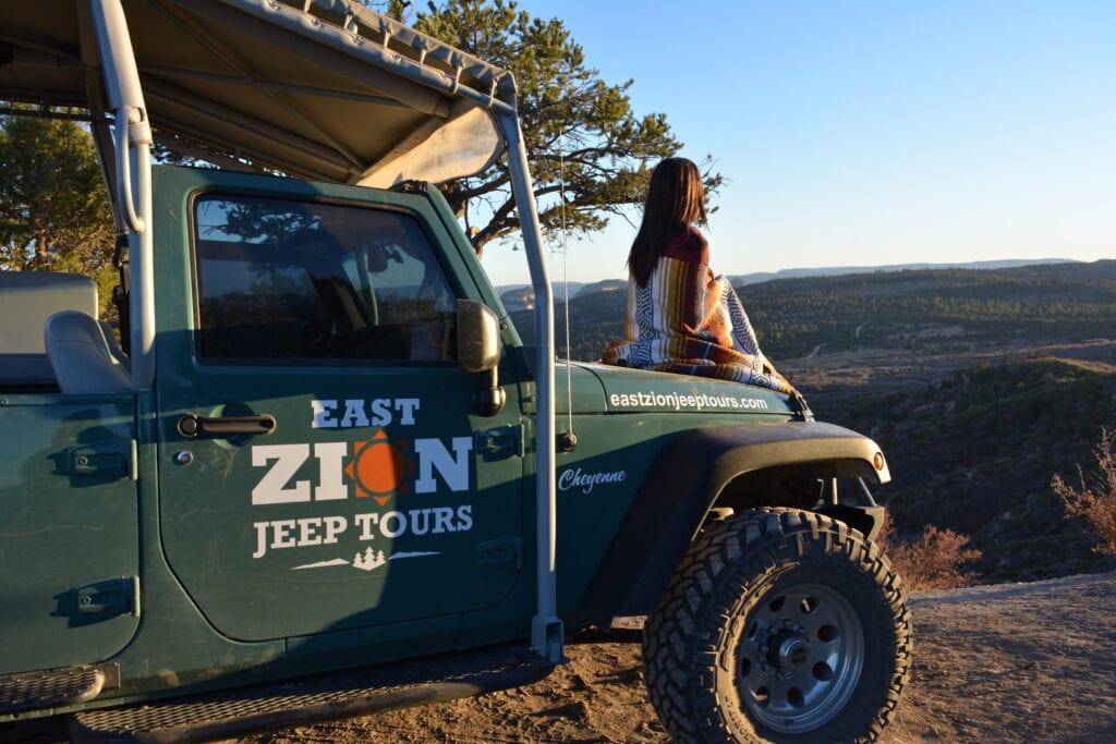 girl sitting on jeep hood at sunrise