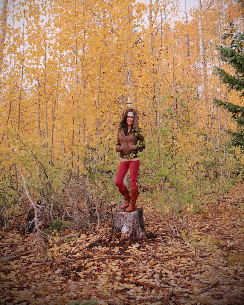 girl standing in the forest on a tree stump with fall leaves