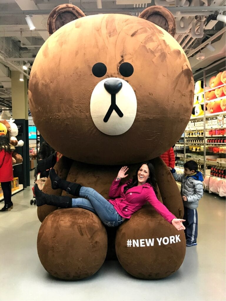 Girl posing on giant teddy bear New York