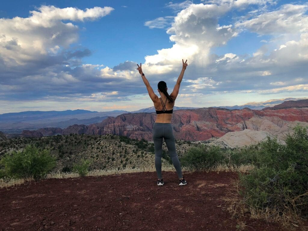 girl standing over mountain overlook with her hands up