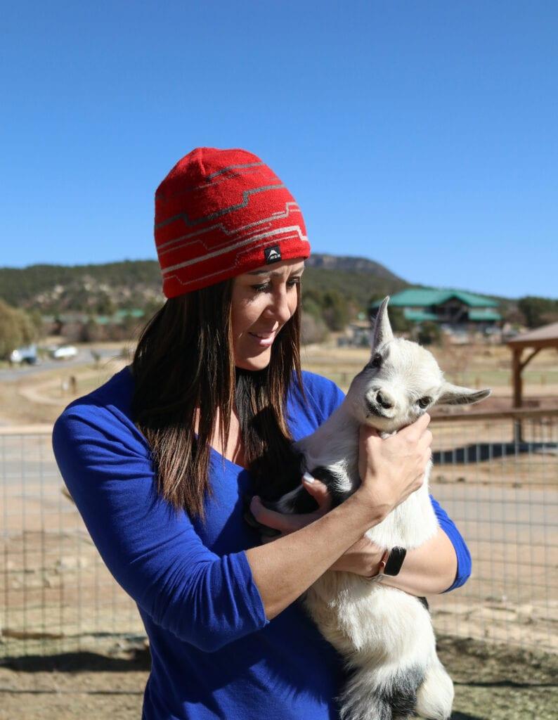 girl holding baby goat